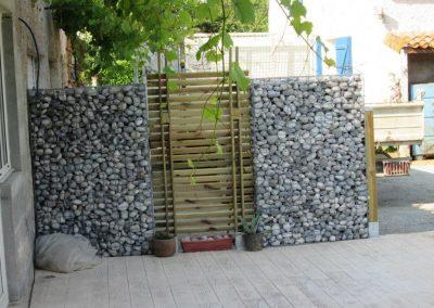 Clôture de gabion avec galets et claustra bois